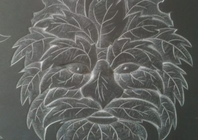 Relief carving of a green man on welsh slate