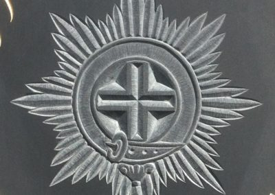 Relief carving of the cold stream guards badge on Welsh slate