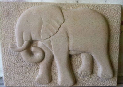 Deep relief carving of a elephant with sparrow pecked background on Portland limestone