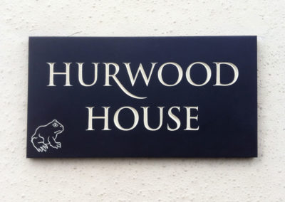 Slate house sign with ivory letters and carved frog design
