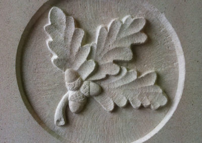 Oak leaf and acorns carved in relief on Portland limestone headstone