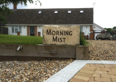 Rustic Limestone boulder house sign with brown letters in place
