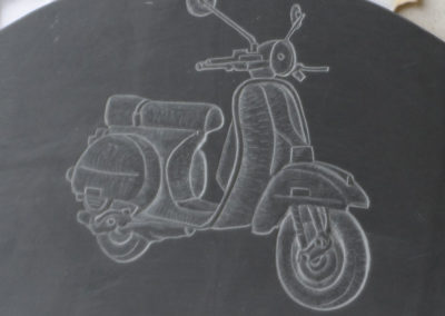 Scooter carved in relief on Welsh slate for a memorial