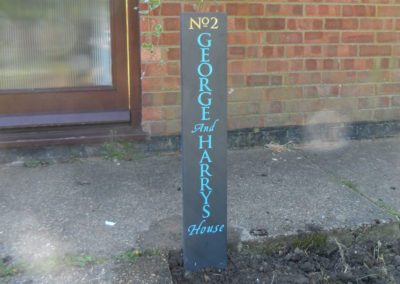 Black slate house sign with blue letters and gilded numbers in place