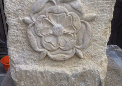 Tudor rose carved on a Rustic sandstone boulder