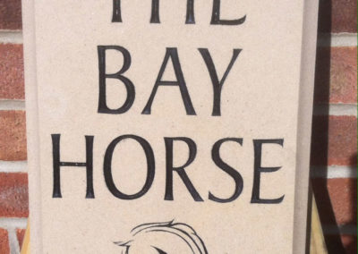 Portland limestone sign with black letters and carved horse head