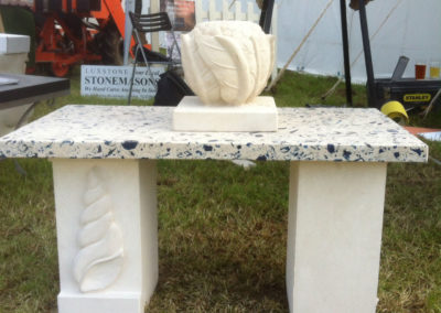 Portland limestone bench with shell carving on the leg